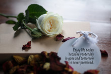 Inspirational Quote - Enjoy Life Today Because Yesterday Is Gone And Tomorrow Is Never Promised. With Petals And White Rose Laying On Messy Table.