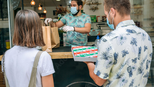 Fototapeta Young couple with mask picking up a take away food order obraz