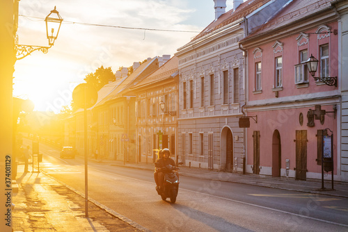 Obraz August 2020, Serbia, Novi Sad, Petrovaradin. A couple on a motorcycle rides through the old city at sunset. Travel to the Balkans - fototapety do salonu