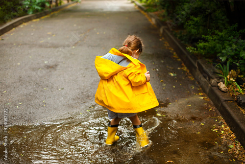 Leinwand Poster Little girl wearing yellow boots in rainy day