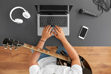 Leisure, Music And People Concept - Young Man Or Musician With Laptop Computer And Guitar Sitting At Table
