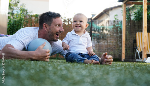 Fényképezés A cute baby and his smiling father playing on a grass with a pilates ball
