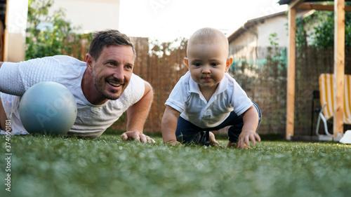 A cute baby and his smiling father playing on a grass with a pilates ball Tapéta, Fotótapéta