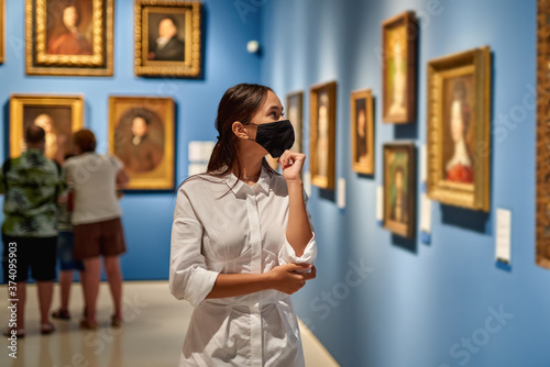 Woman visitor wearing an antivirus mask in the historical museum looking at pictures Fototapeta