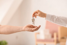 Real Estate Agent Giving Keys From House To New Owner Indoors