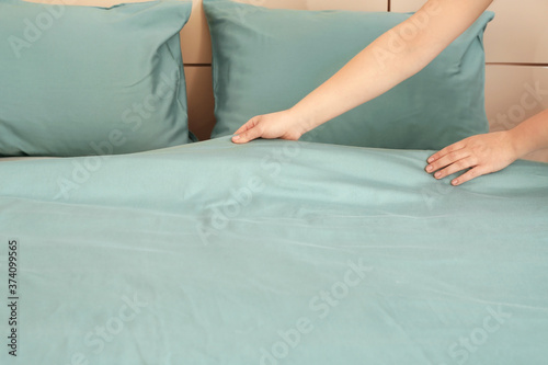 Fototapety, obrazy: Woman making bed at home