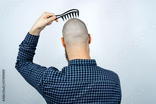 Photo Portrait of back bald man head holding a comb in his hand