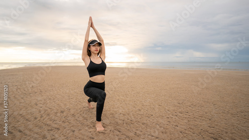 Fotografia, Obraz Woman doing yoga asana low lunge on the beach with sunrise on the morning