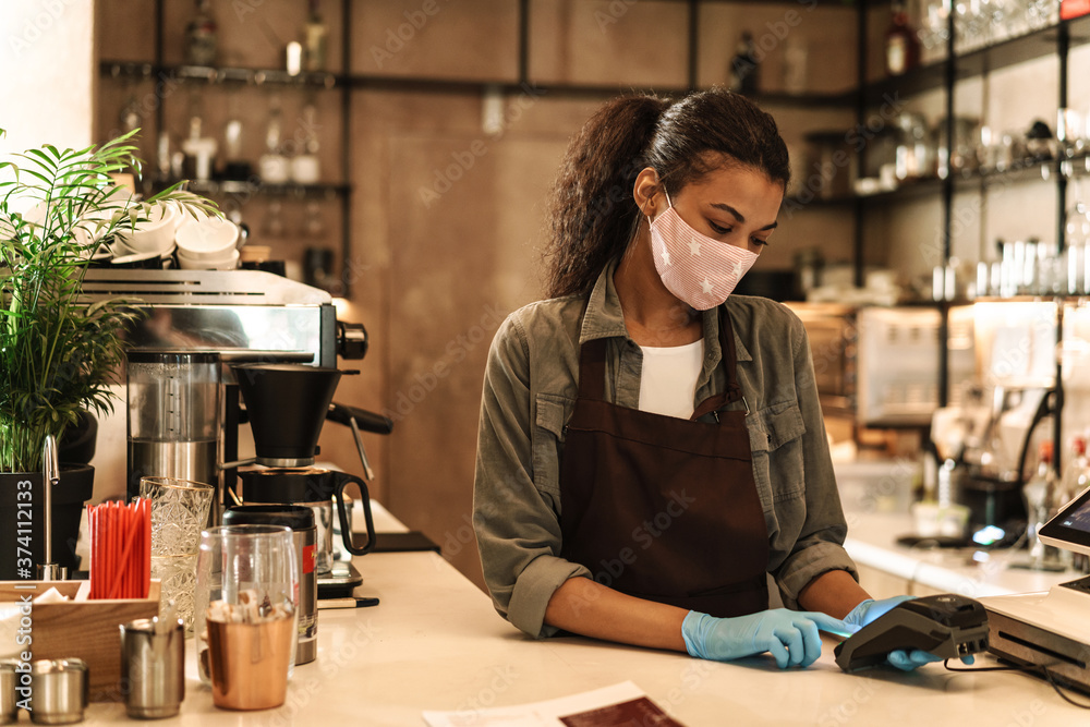 Fototapeta Woman barista wearing medical face mask