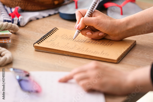 Fotomural Woman making check-list of things to pack for travel