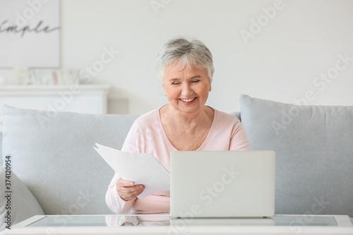 Senior woman with laptop at home Fotobehang