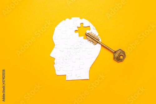 Obraz na plátně Human head made of puzzle pieces and key on color background