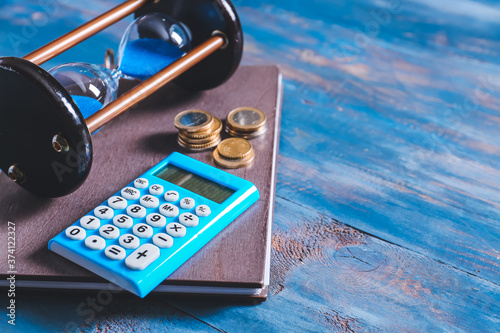 Fotografija Hourglass with calculator and money on color wooden background