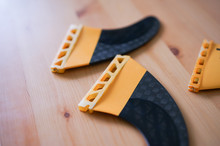 Carbon Fibre Surfboard Fins With Wooden Background