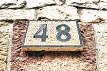 Closeup Shot Of 48 Number On A Wooden Signboard On A Stone Wall