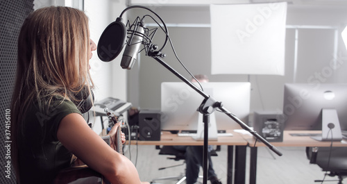 Fotografiet Young woman close up playing guitar recording a song in the studio with blurred background