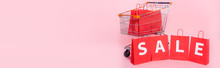 Panoramic Concept Of Word Sale On Red Shopping Bags Near Cart On Pink Surface