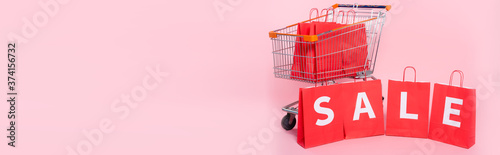 Fototapeta Panoramic concept of word sale on red shopping bags near cart on pink surface obraz