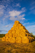 Rollers Made Of Dry Pressed Yellow Straw, Stacked In A Pyramid In A Field, Against A Blue Sky