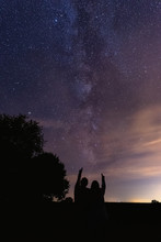 Vertical Shot Of Silhouettes Of A Couple Pointing At The Milky Way In The Night Sky