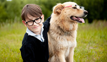 A Schoolboy In Glasses Sits An...