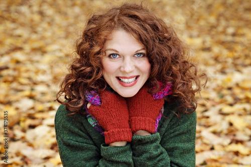 Photo jeune et jolie femme rousse dans un parc arboré en automne avec des feuilles mor