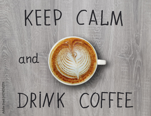 A cup of coffee with whipped cream is on a gray wooden desk. Keep calm and drink coffee.