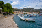 Fototapeta Do pokoju - Hvar/Croatia-August 4th,2020: Beautiful Hvar city with old fortress towering above the town, overlooking the bay and port crowded with ships and boats