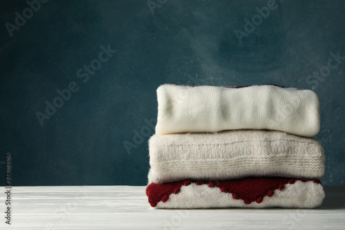 Pile of sweaters on white wooden table against blue background Slika na platnu