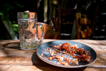 An Empty Glass Of Beer And The Remains Of Crayfish On A Plate That Someone Has Already Eaten