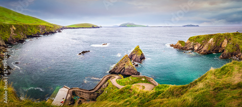 Valokuvatapetti Beautiful view on Dunquin Harbour and small rocky islands with turquoise water and green fields in the background