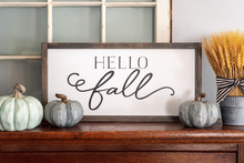 Hello Fall Sign And Neutral Colored Pumpkins On Wood Mantel