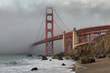The Golden Gate Bridge in downtown San Fransisco covered in fog, as seen from Marshall's Beach