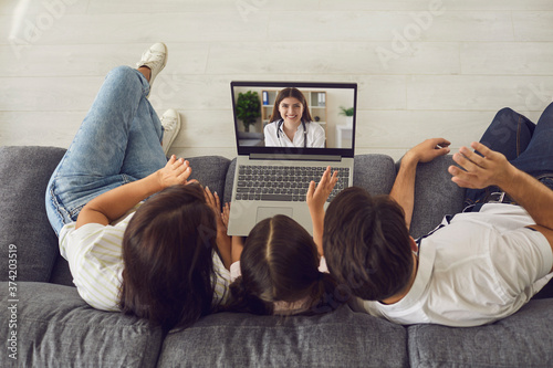 Family with daughter greeting smile doctor online on laptop Poster Mural XXL