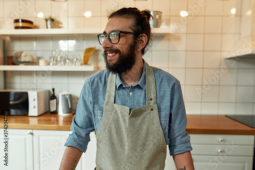 Portrait of young man, Italian cook in apron smiling aside while getting ready to prepare healthy meal with vegetables in the kitchen Fototapet