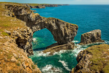 A Dramatic Natural Rock Arch Called The Green Bridge Of Wales And Rock Pillars On The South West Coast Of Pembrokeshire Near Castlemartin In Early Summer