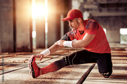 Photo of a young athletic man stretching his legs Canvas