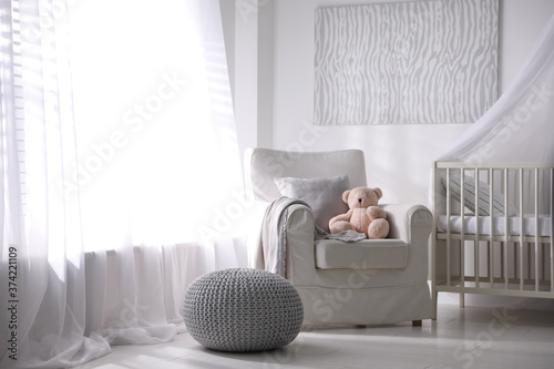 Baby room interior with comfortable crib and armchair Canvas Print