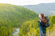 Young woman with backpack enjoys the view of nature at the top of the mountains. Empty space for text