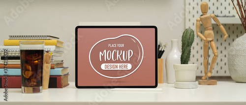 Photo Worktable with mock up laptop , books, stationery, decorations and beverage in h