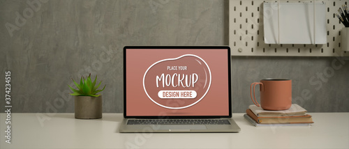 Worktable with mock up laptop, notebooks, mug and decoration in loft living room Canvas Print