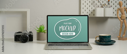 Mock up laptop on worktable with camera, coffee cup and decorations on worktable Canvas Print