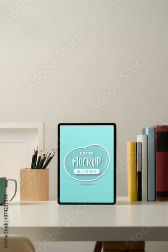 Mock up digital tablet on worktable with stationery, books and decoration in hom Wallpaper Mural