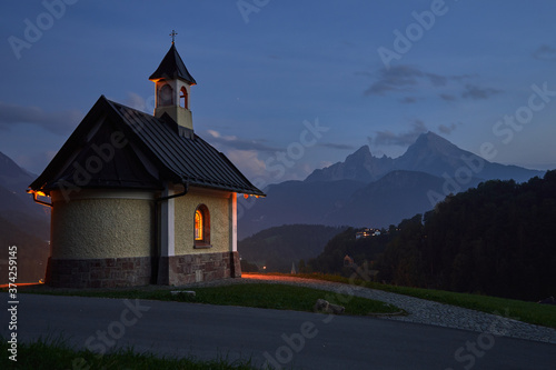 Fotografie, Obraz Traditional Kirchleitn chapel illuminated and Watzmann mountain in the evening i