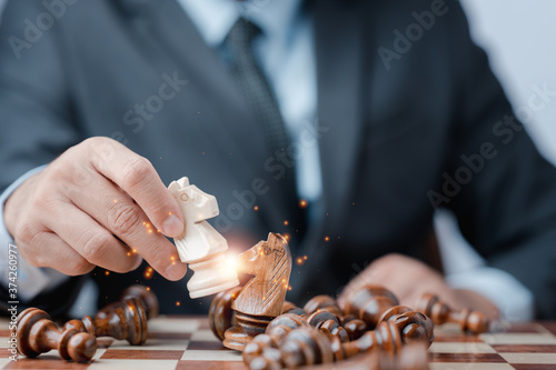 Businessman moving chess piece on chess board game concept for ideas and competition and strategy, business success concept, business competition planing teamwork strategic concept Fototapet