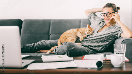 Young female businesswoman student speaks speaks on a mobile phone at home on the couch while working remotely, a ginger cat lies on her