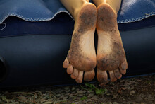 Dirty Cracked Feet Of A Girl Who Lies On A Mattress In The Forest