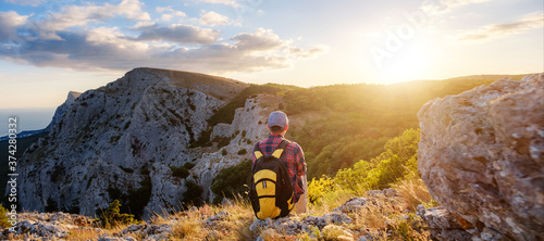 Fotografie, Tablou Adventurous man is on top of the mountain and enjoying the beautiful view during
