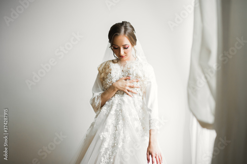Photo Gorgeous bride in robe posing and preparing for the wedding ceremony face in a r