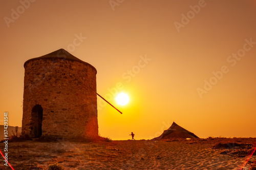 Fototapety, obrazy: Lefkada, Greece. August 18th, 2011. At sunset a kid walks to Milos beach, by the old mill.